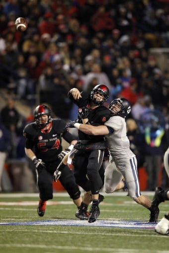 Dec 7, 2013; Fresno, CA, USA; Fresno State Bulldogs quarterback Derek Carr (4) is hit by Utah State Aggies linebacker Kyler Fackrell (9) after throwing a pass in the fourth quarter at Bulldog Stadium. The Bulldogs defeated the Aggies 24-17. Mandatory Credit: Cary Edmondson-USA TODAY Sports