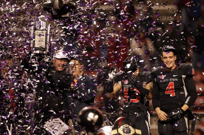 Dec 7, 2013; Fresno, CA, USA; Fresno State Bulldogs head coach Tim DeRuyter holds the Mountain West Championship trophy next to quarterback Derek Carr (4) after the Bulldogs defeated the Utah State Aggies 24-17 at Bulldog Stadium. Mandatory Credit: Cary Edmondson-USA TODAY Sports