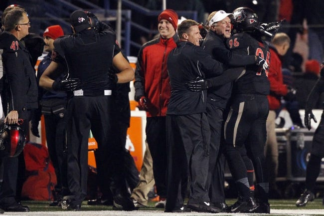 Dec 7, 2013; Fresno, CA, USA; Fresno State Bulldogs head coach Tim DeRuyter is congratulated by defensive end Todd Hunt (96) after the Bulldogs stopped the Utah State Aggies on fourth down in the fourth quarter at Bulldog Stadium. The Bulldogs defeated the Aggies 24-17. Mandatory Credit: Cary Edmondson-USA TODAY Sports