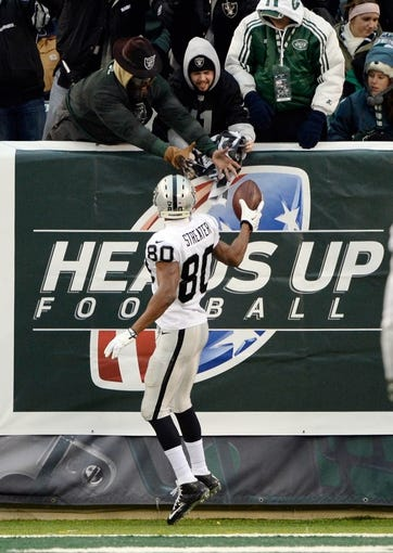 Dec 8, 2013; East Rutherford, NJ, USA; Oakland Raiders wide receiver Rod Streater (80) gives the football to a fan after scoring a touchdown against the New York Jets during the game at MetLife Stadium. Mandatory Credit: Robert Deutsch-USA TODAY Sports