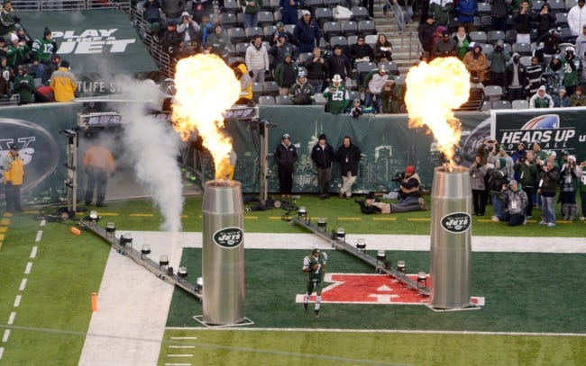 Dec 8, 2013; East Rutherford, NJ, USA; New York Jets quarterback Geno Smith (7) runs onto the field through flames before the game against the Oakland Raiders at MetLife Stadium. The Jets defeated the Raiders 37-27 Mandatory Credit: Kirby Lee-USA TODAY Sports