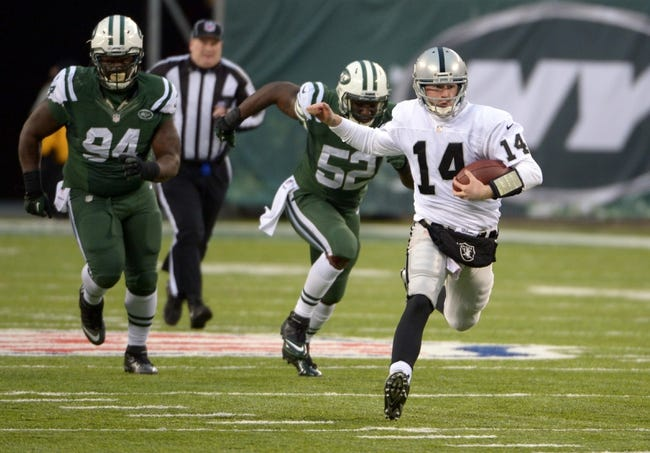 Dec 8, 2013; East Rutherford, NJ, USA; Oakland Raiders quarterback Matt McGloin (14) scrambles from New York Jets defensive lineman Damon Harrison (94) and linebacker David Harris (52) at MetLife Stadium. The Jets defeated the Raiders 37-27 Mandatory Credit: Kirby Lee-USA TODAY Sports