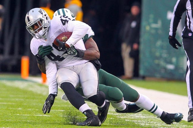 Dec 8, 2013; East Rutherford, NJ, USA; Oakland Raiders fullback Marcel Reece (45) is tackled by New York Jets linebacker David Harris (52) during the second half at MetLife Stadium. The Jets defeated the Raiders 37-27.  Mandatory Credit: Ed Mulholland-USA TODAY Sports