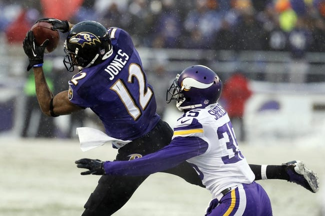 Dec 8, 2013; Baltimore, MD, USA; Baltimore Ravens wide receiver Jacoby Jones (12) makes a fourth quarter catch in front of Minnesota Vikings cornerback Marcus Sherels (35) at M&T Bank Stadium. Mandatory Credit: Mitch Stringer-USA TODAY Sports