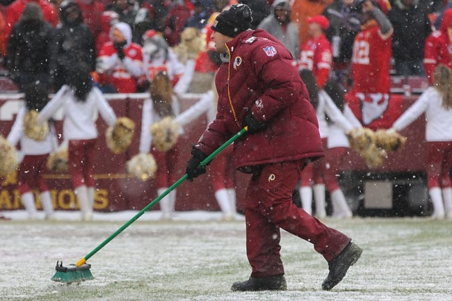 Dec 8, 2013; Landover, MD, USA; A Washington Redskins field worker clears the snow off the field during the game against the Kansas City Chiefs at FedEx Field. The Chiefs won 45-10. Mandatory Credit: Geoff Burke-USA TODAY Sports