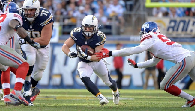 Dec 8, 2013; San Diego, CA, USA; San Diego Chargers running back Danny Woodhead (39) carries the ball as he tries to get past New York Giants outside linebacker Jacquian Williams (57) during first half action at Qualcomm Stadium. Woodhead had 50 receiving yards and 42 yards on the ground in the Chargers win. Mandatory Credit: Robert Hanashiro-USA TODAY Sports