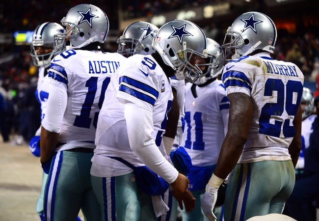 Dec 9, 2013; Chicago, IL, USA; Dallas Cowboys quarterback Tony Romo (9) and teammate huddle around the heater on the sidelines during the third quarter against the Chicago Bears at Soldier Field. Mandatory Credit: Andrew Weber-USA TODAY Sports