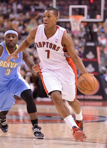 Dec 1, 2013; Toronto, Ontario, CAN; Toronto Raptors point guard Kyle Lowry (7) drives the ball past Denver Nuggets point guard Ty Lawson (3) in the second quarter of a game at the Air Canada Centre. Mandatory Credit: Mark Konezny-USA TODAY Sports