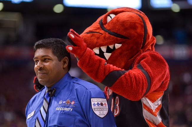 Dec 1, 2013; Toronto, Ontario, CAN; The Toronto Raptors mascot plays with a security guard during a time out in the fourth quarter of a game against the Denver Nuggets at the Air Canada Centre. Denver won the game 112-98. Mandatory Credit: Mark Konezny-USA TODAY Sports