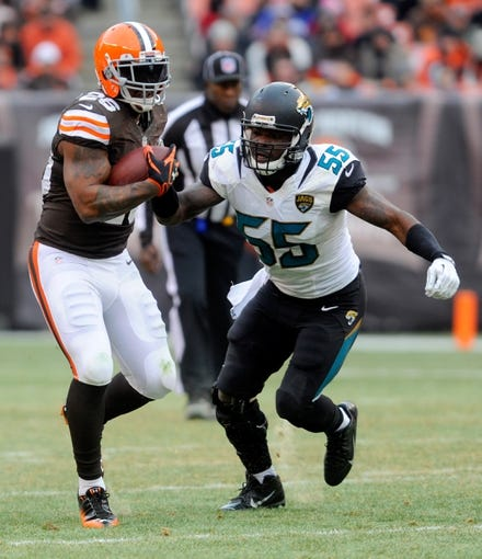 Dec 1, 2013; Cleveland, OH, USA; Cleveland Browns running back Willis McGahee (26) runs by Jacksonville Jaguars outside linebacker Geno Hayes (55) at FirstEnergy Stadium. Mandatory Credit: Ken Blaze-USA TODAY Sports