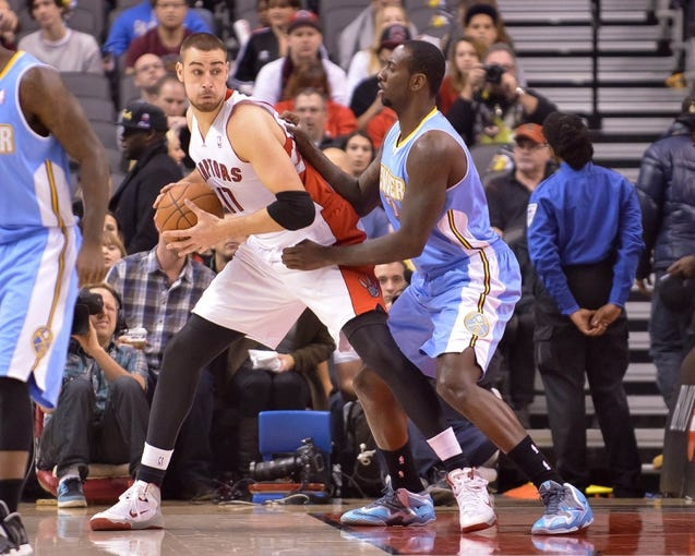 Dec 1, 2013; Toronto, Ontario, CAN; Toronto Raptors center Jonas Valanciunas (17) looks to dribble the ball past Denver Nuggets power forward J.J. Hickson (7) in the first quarter of a game at the Air Canada Centre. Mandatory Credit: Mark Konezny-USA TODAY Sports