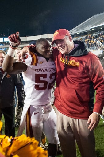 Nov 30, 2013; Morgantown, WV, USA; Iowa State Cyclones linebacker Jeremiah George (52) and head coach Paul Rhoads embrace after the defense stop West Virginia Mountaineers offense in the third overtime at Milan Puskar Stadium. The Iowa State Cyclones defeated West Virginia Mountaineers 52-44 in the third overtime. Mandatory Credit: Tommy Gilligan-USA TODAY Sports