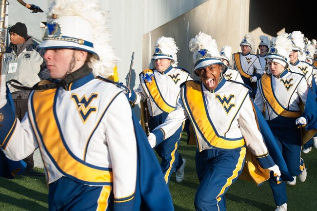 Nov 30, 2013; Morgantown, WV, USA; A member of the West Virginia Mountaineers band shows her excitement as she runs onto the field for the pre-game performance at Milan Puskar Stadium. The Iowa State Cyclones defeated West Virginia Mountaineers 52-44 in the third overtime. Mandatory Credit: Tommy Gilligan-USA TODAY Sports