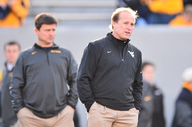 Nov 30, 2013; Morgantown, WV, USA; West Virginia Mountaineers head coach Dana Holgorsen watches his team go through pre game drills prior to the start of the game against Iowa State Cyclones at Milan Puskar Stadium. The Iowa State Cyclones defeated West Virginia Mountaineers 52-44 in the third overtime. Mandatory Credit: Tommy Gilligan-USA TODAY Sports