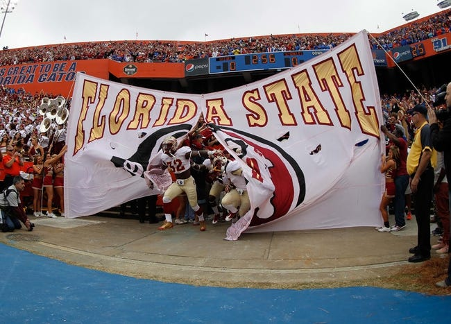 Nov 30, 2013; Gainesville, FL, USA; Florida State Seminoles running back James Wilder Jr. (32) and teammates run out of the banner onto the field before the game against the Florida Gators at Ben Hill Griffin Stadium. Mandatory Credit: Kim Klement-USA TODAY Sports