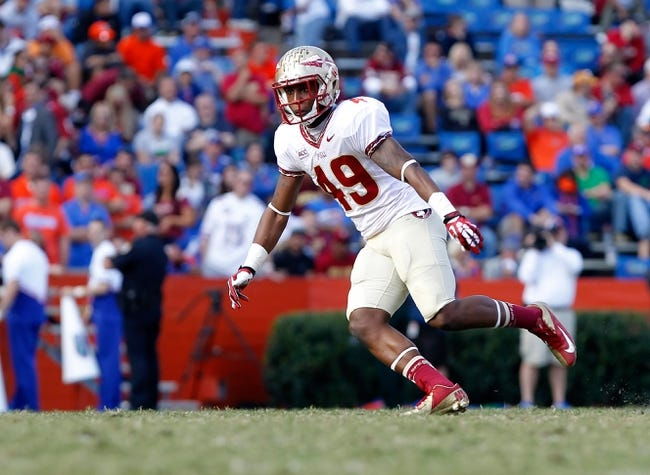 Nov 30, 2013; Gainesville, FL, USA; Florida State Seminoles defensive back Colton Woodall (49) rushes against the Florida Gators during the second half at Ben Hill Griffin Stadium. Florida State Seminoles defeated the Florida Gators 37-7. Mandatory Credit: Kim Klement-USA TODAY Sports