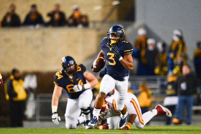 Nov 30, 2013; Morgantown, WV, USA; West Virginia Mountaineers running back Charles Sims (3) runs with the ball for a touchdown during the third quarter of the game against Iowa State Cyclones at Milan Puskar Stadium. The Iowa State Cyclones defeated West Virginia Mountaineers 52-44 in the third overtime. Mandatory Credit: Tommy Gilligan-USA TODAY Sports