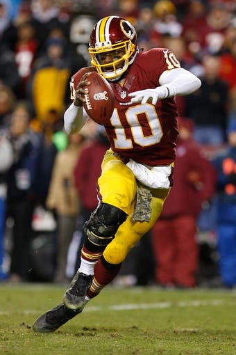 Nov 25, 2013; Landover, MD, USA; Washington Redskins quarterback Robert Griffin III (10) runs with the ball against the San Francisco 49ers at FedEx Field. Mandatory Credit: Geoff Burke-USA TODAY Sports