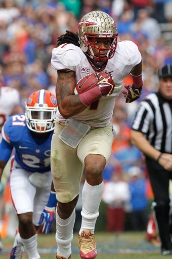 Nov 30, 2013; Gainesville, FL, USA; Florida State Seminoles wide receiver Kelvin Benjamin (1) runs the ball for a touchdown during the second quarter against the Florida Gators at Ben Hill Griffin Stadium. Mandatory Credit: Kim Klement-USA TODAY Sports