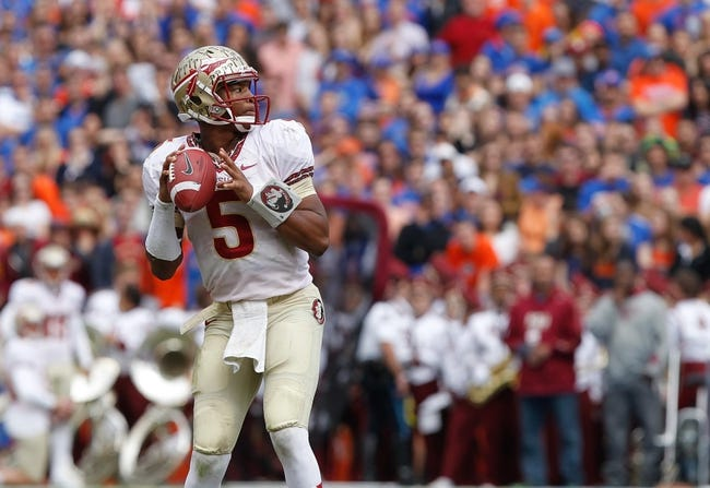 Nov 30, 2013; Gainesville, FL, USA; Florida State Seminoles quarterback Jameis Winston (5) drops back to throw the ball for a touchdown against the Florida Gators  during the second quarter at Ben Hill Griffin Stadium. Mandatory Credit: Kim Klement-USA TODAY Sports