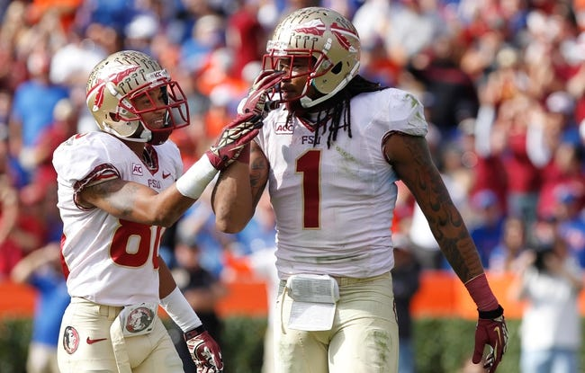 Nov 30, 2013; Gainesville, FL, USA; Florida State Seminoles wide receiver Kelvin Benjamin (1) is congratulated by wide receiver Rashad Greene (80) after catching the ball against the Florida Gators during the second half at Ben Hill Griffin Stadium. Florida State Seminoles defeated the Florida Gators 37-7. Mandatory Credit: Kim Klement-USA TODAY Sports