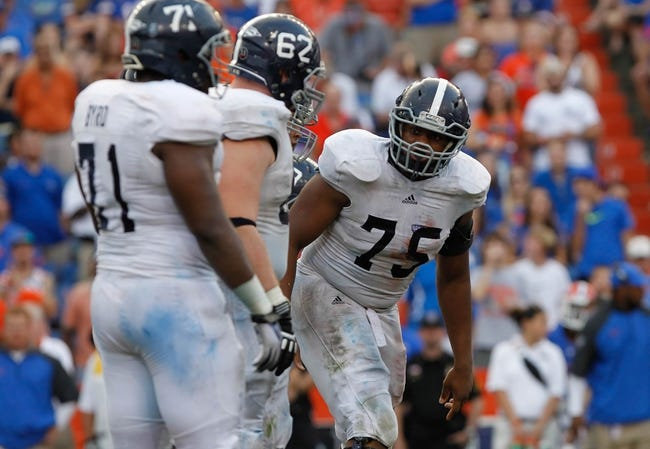 Nov 23, 2013; Gainesville, FL, USA; Georgia Southern Eagles center Manrey Saint-Amour (75) talks with guard Zach Lonas (62) and  offensive tackle Dorian Byrd (71) during the second half at Ben Hill Griffin Stadium. Georgia Southern Eagles defeated the Florida Gators 26-20. Mandatory Credit: Kim Klement-USA TODAY Sports