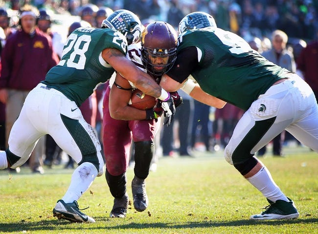 Nov 30, 2013; East Lansing, MI, USA; Minnesota Golden Gophers running back David Cobb (27) is tackled by Michigan State Spartans linebacker Denicos Allen (28) and Michigan State Spartans defensive end Demetrius Cooper (98) during the 1st half a game at Spartan Stadium. Mandatory Credit: Mike Carter-USA TODAY Sports