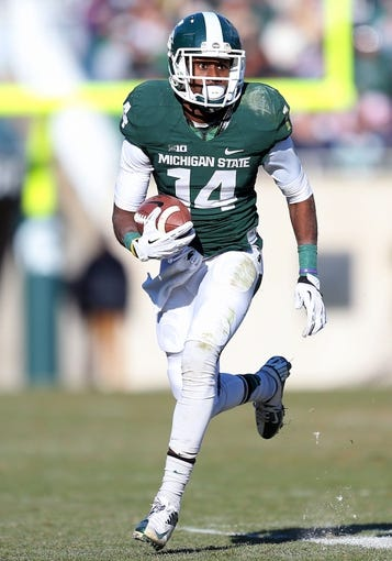 Nov 30, 2013; East Lansing, MI, USA; Michigan State Spartans wide receiver Tony Lippett (14) runs for yards after the catch during the 2nd half a game against the Minnesota Golden Gophers at Spartan Stadium. MSU won 14-3.  Mandatory Credit: Mike Carter-USA TODAY Sports