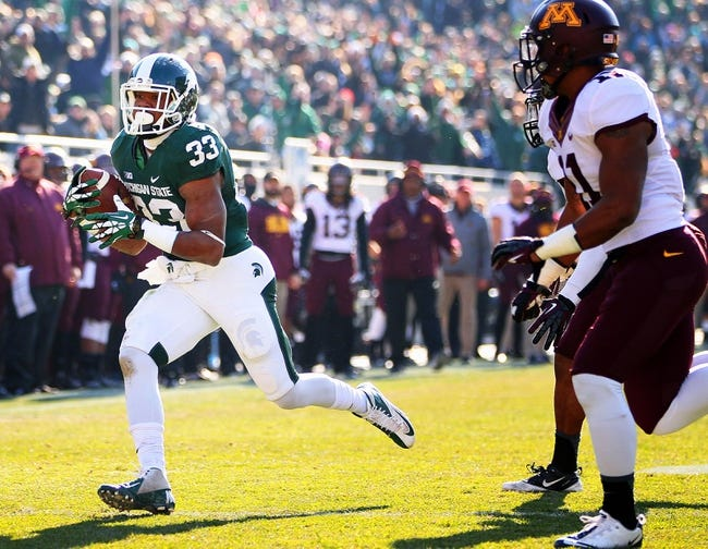 Nov 30, 2013; East Lansing, MI, USA; Michigan State Spartans running back Jeremy Langford (33) runs the ball against Minnesota Golden Gophers during the 1st half a game at Spartan Stadium. Mandatory Credit: Mike Carter-USA TODAY Sports