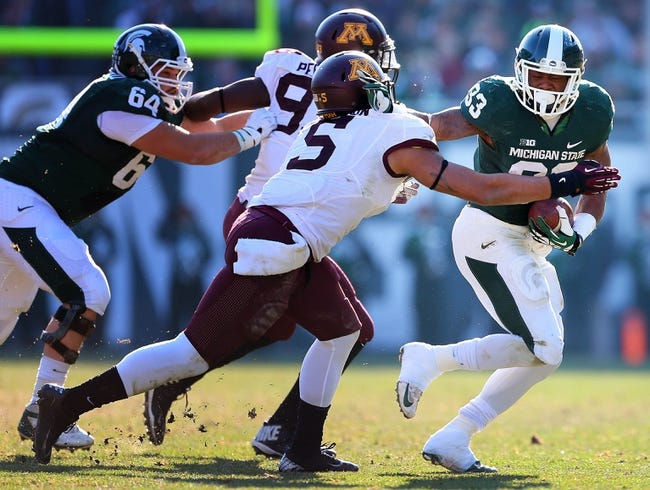 Nov 30, 2013; East Lansing, MI, USA; Michigan State Spartans running back Jeremy Langford (33) tries to get outside of Minnesota Golden Gophers linebacker Damien Wilson (5) during the 1st half a game at Spartan Stadium. Mandatory Credit: Mike Carter-USA TODAY Sports
