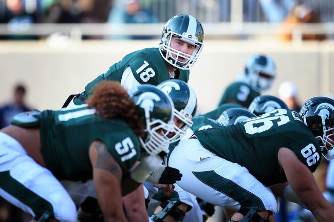 Nov 30, 2013; East Lansing, MI, USA; Michigan State Spartans quarterback Connor Cook (18) looks down offensive line during the 1st half a against the Minnesota Golden Gophers game at Spartan Stadium. Mandatory Credit: Mike Carter-USA TODAY Sports
