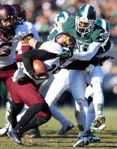Nov 30, 2013; East Lansing, MI, USA; Minnesota Golden Gophers wide receiver Devon Wright (25) is tackled by Michigan State Spartans cornerback Jermaine Edmondson (39) during the 2nd half a game at Spartan Stadium. MSU won 14-3.  Mandatory Credit: Mike Carter-USA TODAY Sports