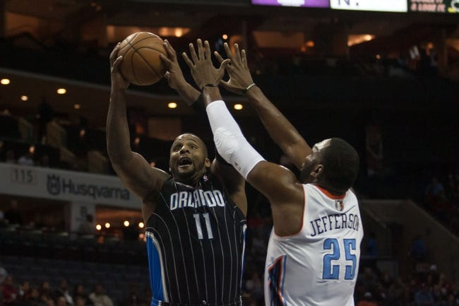 Dec 11, 2013; Charlotte, NC, USA; Orlando Magic power forward Glen Davis (11) goes up for a shot over Charlotte Bobcats center Al Jefferson (25) during the first half at Time Warner Cable Arena. Mandatory Credit: Jeremy Brevard-USA TODAY Sports