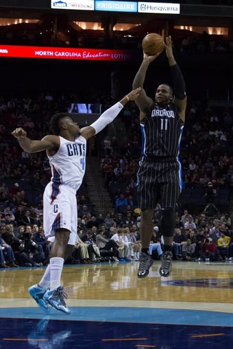 Dec 11, 2013; Charlotte, NC, USA; Orlando Magic power forward Glen Davis (11) shoots the ball over Charlotte Bobcats power forward Jeff Adrien (4) during the first half at Time Warner Cable Arena. Mandatory Credit: Jeremy Brevard-USA TODAY Sports