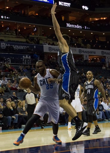 Dec 11, 2013; Charlotte, NC, USA; Charlotte Bobcats center Al Jefferson (25) drives the ball inside against Orlando Magic center Nikola Vucevic (9) during the second half at Time Warner Cable Arena. The Magic defeated the Bobcats 92-83. Mandatory Credit: Jeremy Brevard-USA TODAY Sports