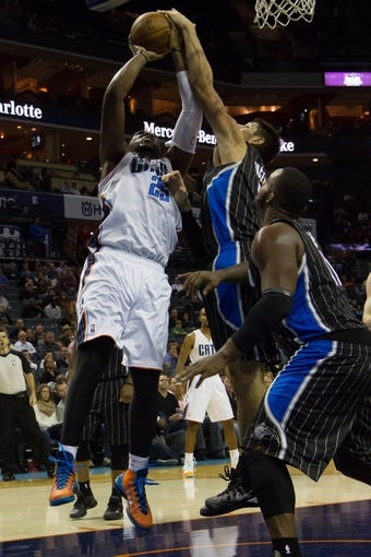Dec 11, 2013; Charlotte, NC, USA; Charlotte Bobcats center Al Jefferson (25) tries to shoot the ball over Orlando Magic center Nikola Vucevic (9) during the second half at Time Warner Cable Arena. The Magic defeated the Bobcats 92-83. Mandatory Credit: Jeremy Brevard-USA TODAY Sports