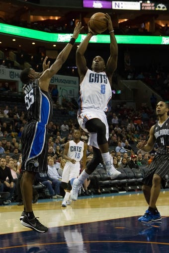 Dec 11, 2013; Charlotte, NC, USA; Charlotte Bobcats shooting guard Ben Gordon (8) goes up for a shot while Orlando Magic point guard E'Twaun Moore (55) defends during the second half at Time Warner Cable Arena. The Magic defeated the Bobcats 92-83. Mandatory Credit: Jeremy Brevard-USA TODAY Sports