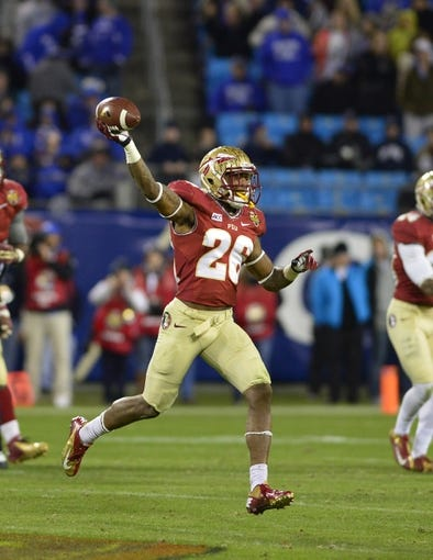 Dec 7, 2013; Charlotte, NC, USA; Florida State Seminoles defensive back P.J. Williams (26) reacts with the ball in the third quarter at Bank of America Stadium. Mandatory Credit: Bob Donnan-USA TODAY Sports