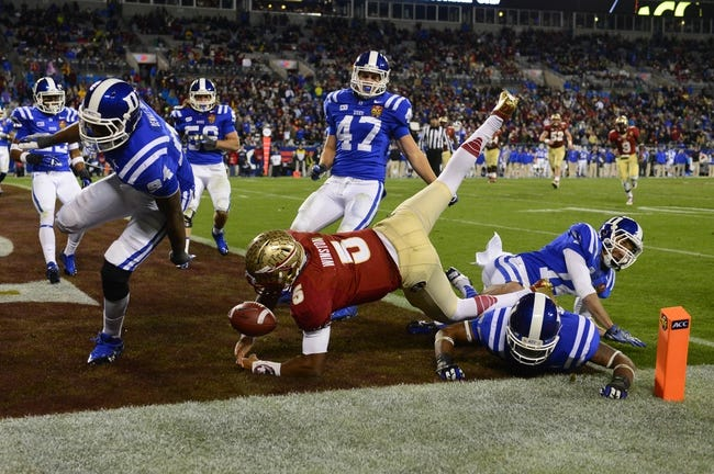 Dec 7, 2013; Charlotte, NC, USA; Florida State Seminoles quarterback Jameis Winston (5) scores a touchdown as Duke Blue Devils cornerback Bryon Fields (14) and linebacker David Helton (47) and defensive end Kenny Anunike (84) and safety Dwayne Norman (40) defend in the third quarter at Bank of America Stadium. Mandatory Credit: Bob Donnan-USA TODAY Sports