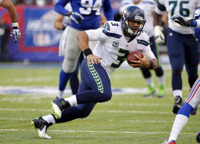 Dec 15, 2013; East Rutherford, NJ, USA;  Seattle Seahawks quarterback Russell Wilson (3) scrambles for a first down during the first half against the New York Giants at MetLife Stadium. Mandatory Credit: Jim O'Connor-USA TODAY Sports
