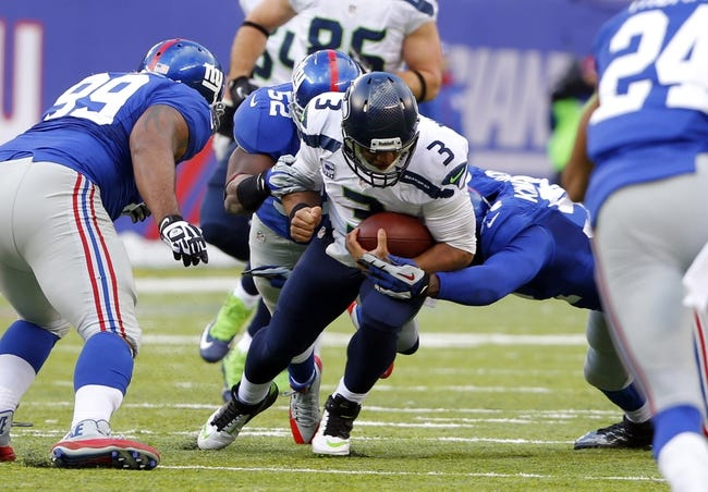 Dec 15, 2013; East Rutherford, NJ, USA;  Seattle Seahawks quarterback Russell Wilson (3) is brought down by New York Giants middle linebacker Jon Beason (52) and defensive end Mathias Kiwanuka (right) at MetLife Stadium. Mandatory Credit: Jim O'Connor-USA TODAY Sports