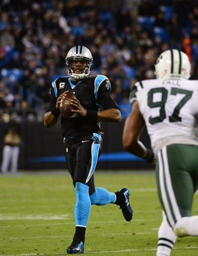 Dec 15, 2013; Charlotte, NC, USA; Carolina Panthers quarterback Cam Newton (1) with the ball as New York Jets outside linebacker Calvin Pace (97) pressures in the third quarter at Bank of America Stadium. Mandatory Credit: Bob Donnan-USA TODAY Sports