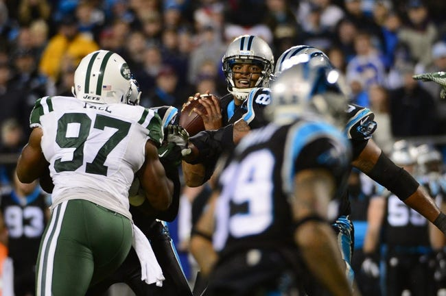 Dec 15, 2013; Charlotte, NC, USA; Carolina Panthers quarterback Cam Newton (1) looks to pass as New York Jets outside linebacker Calvin Pace (97) pressures in the third quarter at Bank of America Stadium. Mandatory Credit: Bob Donnan-USA TODAY Sports