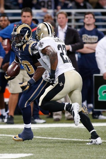 Dec 15, 2013; St. Louis, MO, USA;  St. Louis Rams running back Zac Stacy (30) carries the ball while under pressure from New Orleans Saints free safety Malcolm Jenkins (27) at the Edward Jones Dome. Mandatory Credit: Scott Kane-USA TODAY Sports
