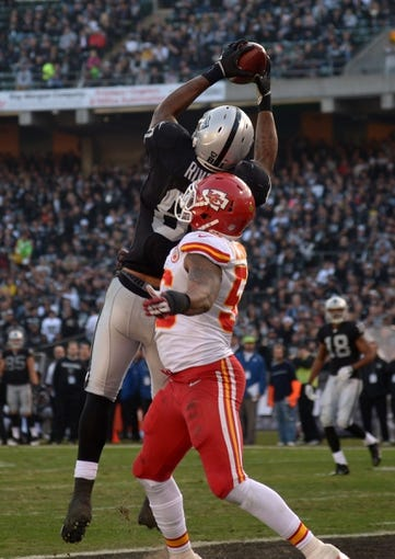 Dec 15, 2013; Oakland, CA, USA; Oakland Raiders tight end Mychal Rivera (81) is defended by Kansas City Chiefs linebacker James-Michael Johnson (52) on a 14-yard touchdown reception in the third quarter at O.co Coliseum. The Chiefs defeated the Raiders 56-31. Mandatory Credit: Kirby Lee-USA TODAY Sports
