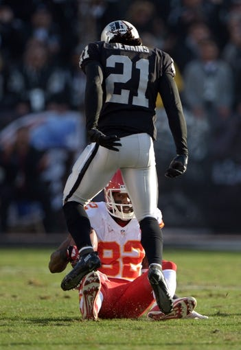 Dec 15, 2013; Oakland, CA, USA; Oakland Raiders cornerbacks Mike Jenkins (21) reacts after tackling Kansas City Chiefs receiver Dwayne Bowe (82) at O.co Coliseum. The Chiefs defeated the Raiders 56-31. Mandatory Credit: Kirby Lee-USA TODAY Sports