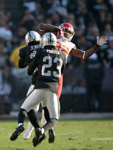 Dec 15, 2013; Oakland, CA, USA; Oakland Raiders cornerbacks Mike Jenkins (21) and Tracy Porter (23) tackle Kansas City Chiefs receiver Dwayne Bowe (82) at O.co Coliseum. The Chiefs defeated the Raiders 56-31. Mandatory Credit: Kirby Lee-USA TODAY Sports