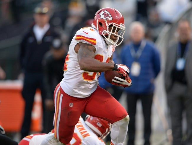 Dec 15, 2013; Oakland, CA, USA; Kansas City Chiefs running back Knile Davis (34) scores on a 17-yard touchdown run against the Oakland Raiders at O.co Coliseum. The Chiefs defeated the Raiders 56-31. Mandatory Credit: Kirby Lee-USA TODAY Sports