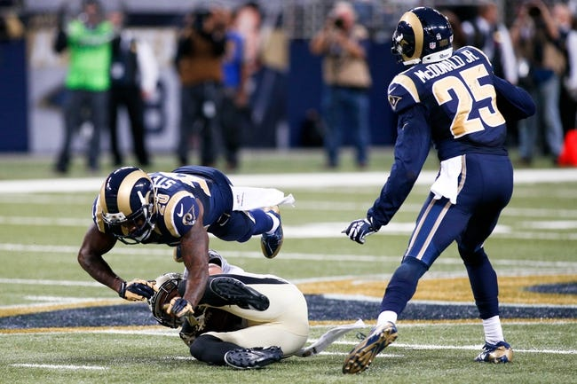 Dec 15, 2013; St. Louis, MO, USA;  St. Louis Rams strong safety Darian Stewart (20) leaps over New Orleans Saints wide receiver Lance Moore (16) as strong safety T.J. McDonald (25) looks on during the second half at the Edward Jones Dome. Mandatory Credit: Scott Kane-USA TODAY Sports