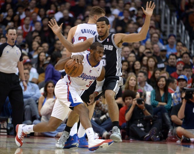 Dec 16, 2013; Los Angeles, CA, USA; Los Angeles Clippers guard Chris Paul (3) is defended by San Antonio Spurs guard Cory Joseph (5) at Staples Center. The Clippers defeated the Spurs 115-92. Mandatory Credit: Kirby Lee-USA TODAY Sports